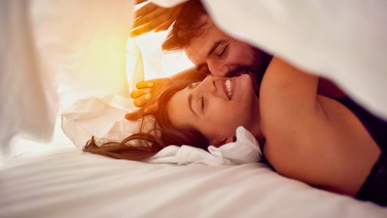 Happy young couple having fun in bed